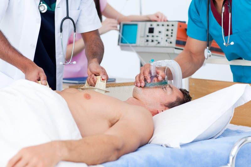 Geconcentreerd medisch team dat een patiënt reanimeert stock fotografie
