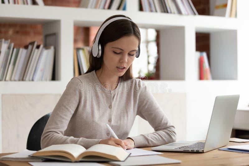 Geconcentreerd meisje die in Bluetooth-hoofdtelefoons thuis bestuderen royalty-vrije stock afbeeldingen