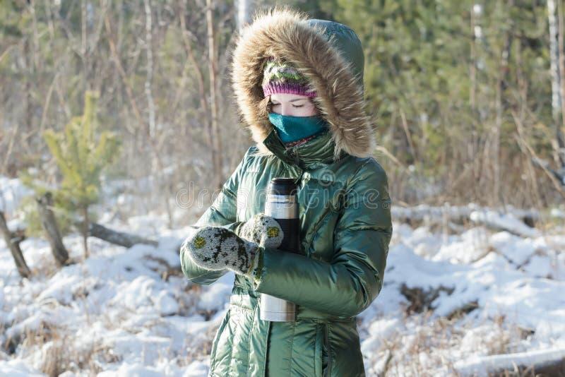 Geconcentreerd meisje die groene glanzende benedenlaag het openen roestvrij staalthermosfles in de winter ijzig hout in openlucht stock afbeeldingen