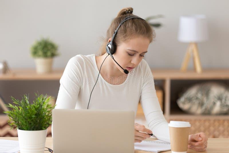 Geconcentreerd meisje die in hoofdtelefoon met laptop thuis bestuderen stock afbeelding