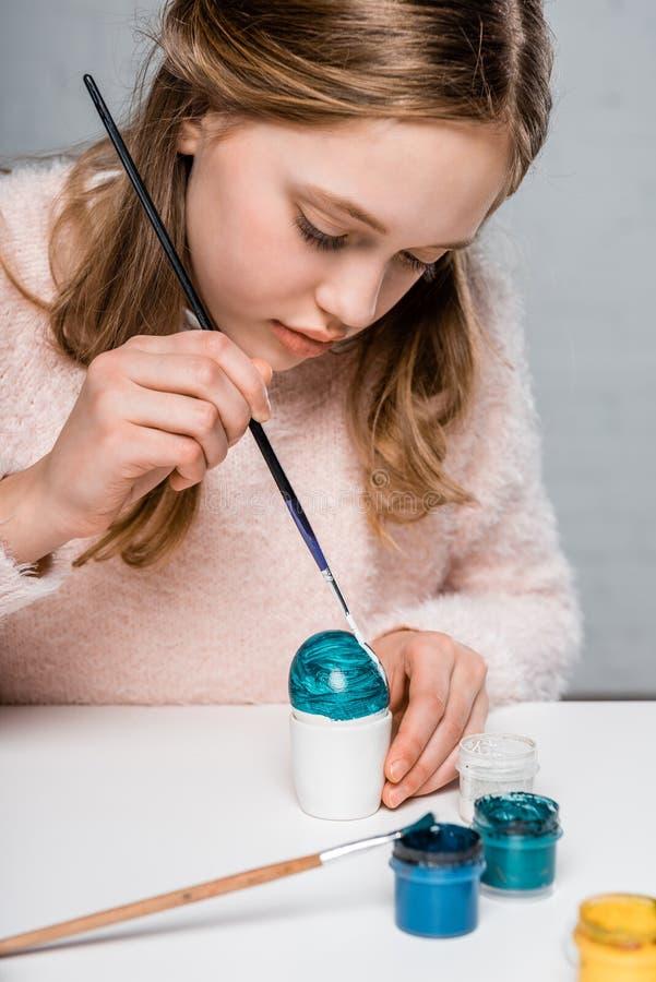 Geconcentreerd meisje die paasei schilderen royalty-vrije stock afbeeldingen