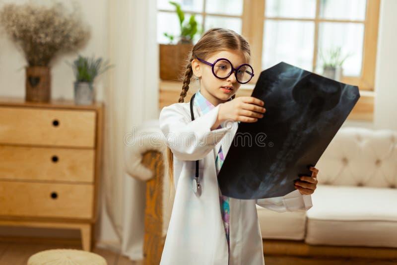 Geconcentreerd meisje die in witte laag de röntgenstraal in handen houden stock foto