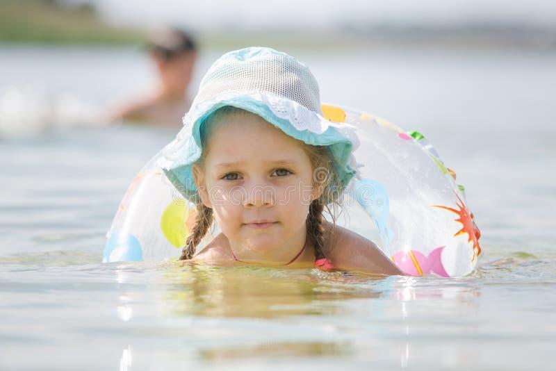 Geconcentreerd meisje van vier jaar met een cirkel die in de rivier drijven royalty-vrije stock afbeeldingen