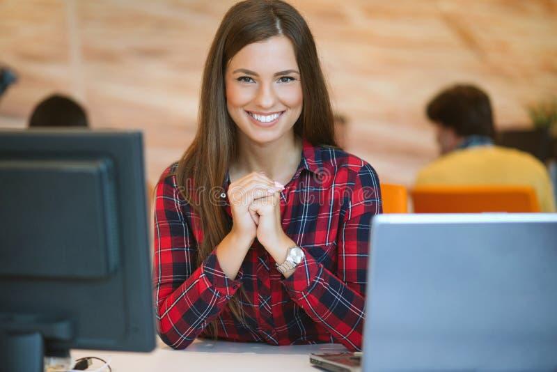 Geconcentreerd op het werk Jonge mooie vrouw die haar laptop met behulp van terwijl het zitten als voorzitter op haar werkende pl royalty-vrije stock afbeeldingen