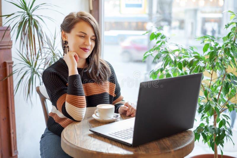 Geconcentreerd op het werk Zekere jonge vrouw die in slimme vrijetijdskleding aan laptop werken terwijl het zitten dichtbij venst royalty-vrije stock afbeelding