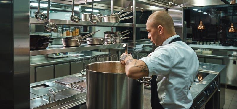 Geconcentreerd op zijn werk Zijaanzicht van beroemde jonge chef-kok met tatoegeringen op zijn wapens die een soep in een restaura royalty-vrije stock afbeelding