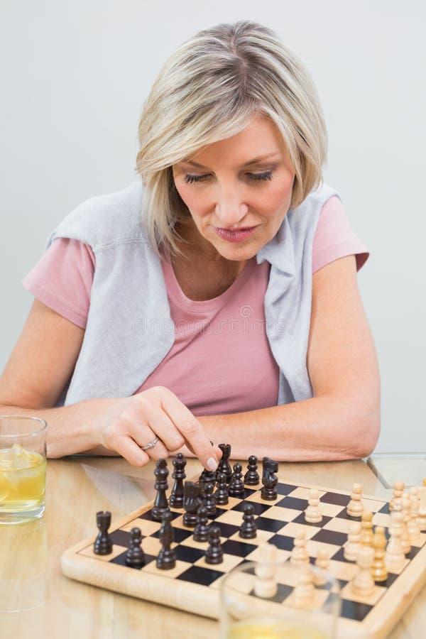 Geconcentreerd vrouw het spelen schaak bij lijst stock afbeelding