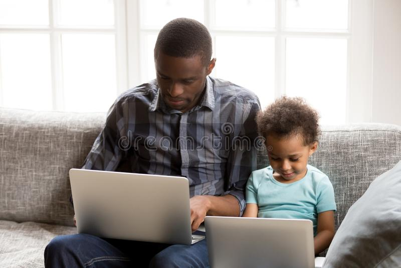 Geconcentreerde Afrikaanse Amerikaanse familie die laptops samen thuis met behulp van stock foto