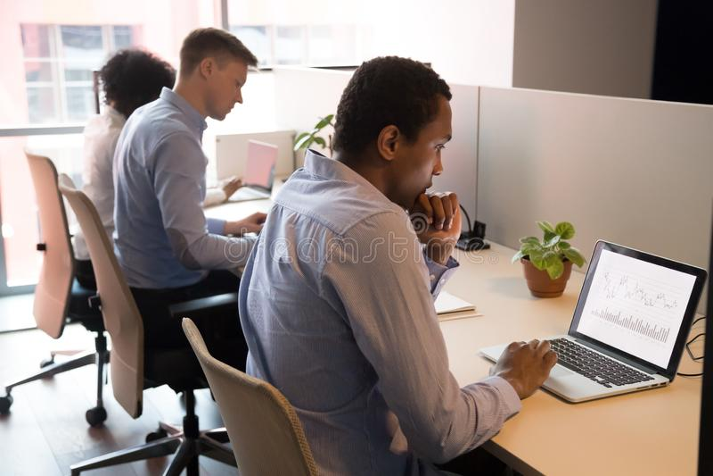 Geconcentreerde Afrikaanse Amerikaanse zakenman die aan laptop in bureau werken stock foto's