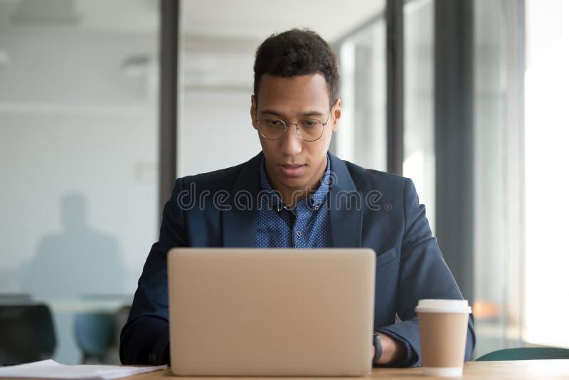 Geconcentreerde Afrikaanse Amerikaanse zakenman die bij laptop in bureau werken royalty-vrije stock fotografie