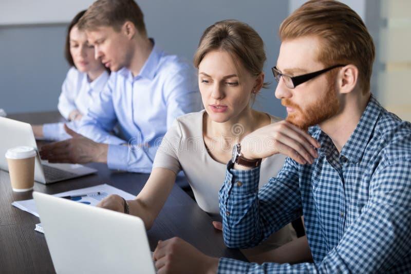 Geconcentreerde arbeiders bezig bij laptops die bedrijfsproject bespreken royalty-vrije stock afbeelding