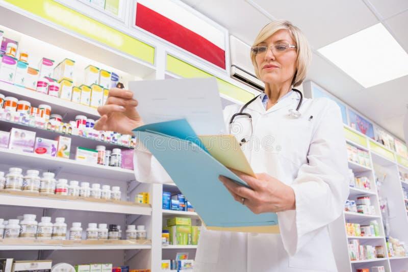 Geconcentreerde arts die een voorschrift lezen stock foto's
