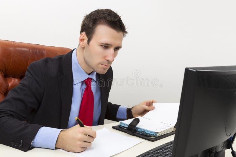 Geconcentreerde bedrijfsmens die een document document vullen stock fotografie