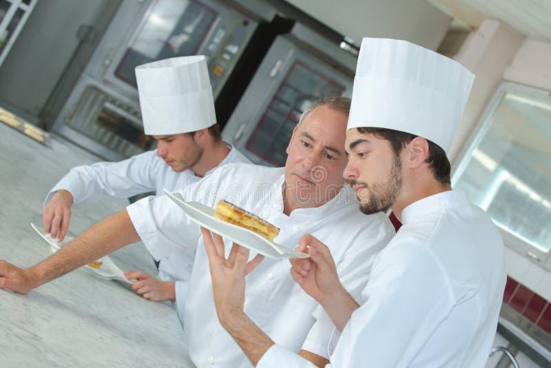 Geconcentreerde chef-kok die cake in restaurantkeuken voorbereiden royalty-vrije stock foto