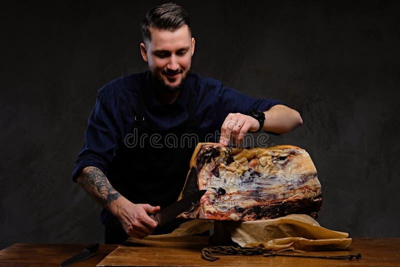 Geconcentreerde chef-kokkok die exclusief schokkerig vlees op een lijst in een de jachthuis snijden op donkere achtergrond stock afbeelding