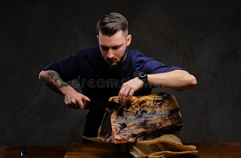 Geconcentreerde chef-kokkok die exclusief schokkerig vlees op een lijst in een de jachthuis snijden op donkere achtergrond stock foto's