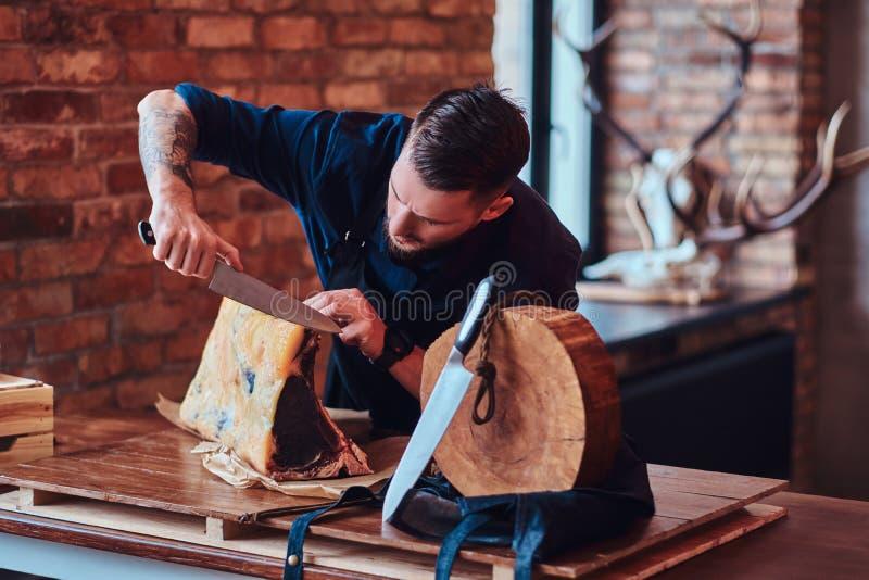 Geconcentreerde chef-kokkok die exclusief schokkerig vlees op een lijst in keuken met zolderbinnenland snijden royalty-vrije stock foto's