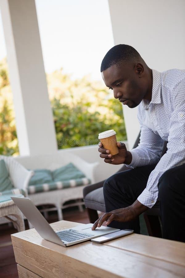 Geconcentreerde de koffiekop van de zakenmanholding terwijl het gebruiken van laptop royalty-vrije stock afbeeldingen