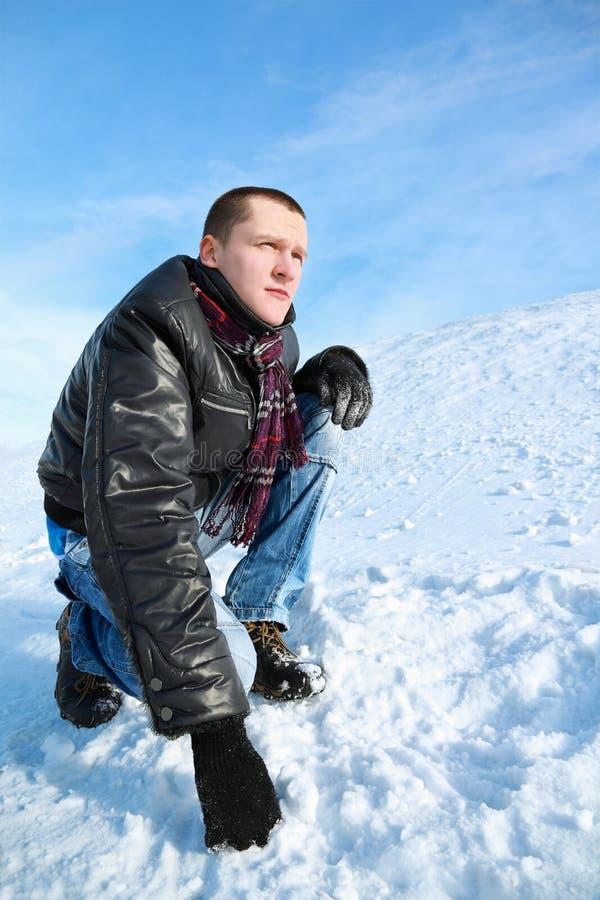 Geconcentreerde de mens kijkt de winter van het hurken in hemel stock fotografie