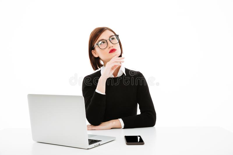 Geconcentreerde denkende jonge bedrijfsdame die laptop met behulp van royalty-vrije stock fotografie