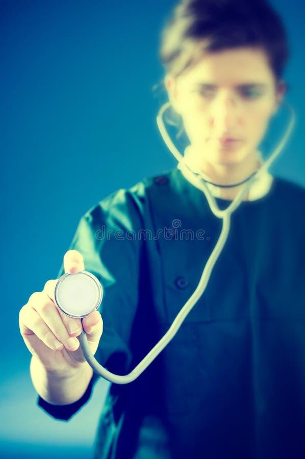 Geconcentreerde dokter met stethoscoop stock foto's