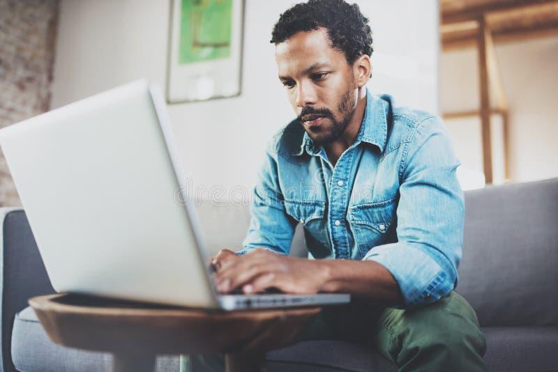 Geconcentreerde gebaarde Afrikaanse mens die thuis terwijl het zitten op de bank werken Concept jongeren die mobiele apparaten me royalty-vrije stock afbeeldingen