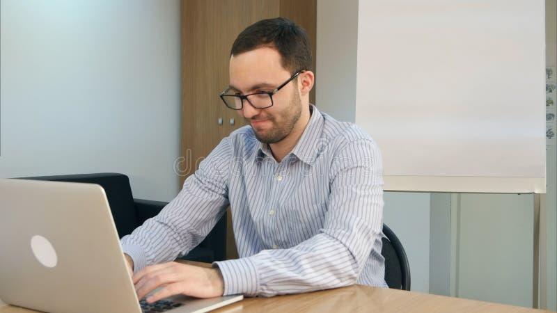 Geconcentreerde gebaarde jonge mens die laptop voor het bestuderen met behulp van stock foto