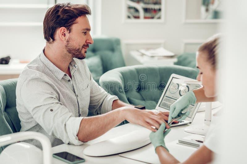Geconcentreerde gebaarde kerel in licht overhemd die informatie over laptop controleren royalty-vrije stock afbeelding