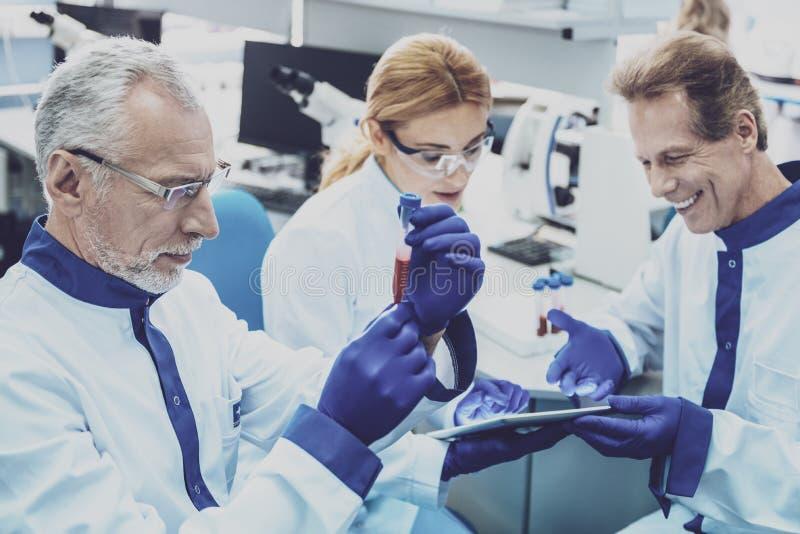 Geconcentreerde gebaarde wetenschapper die reagens bekijken stock foto's