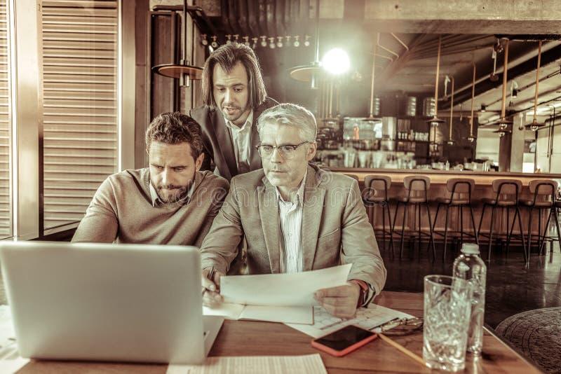 Geconcentreerde grijs-haired arbeider die aan zijn partners luisteren royalty-vrije stock afbeelding