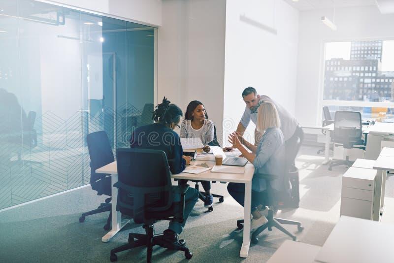 Geconcentreerde groep bedrijfscollega's die een bureauvergadering hebben aan royalty-vrije stock foto