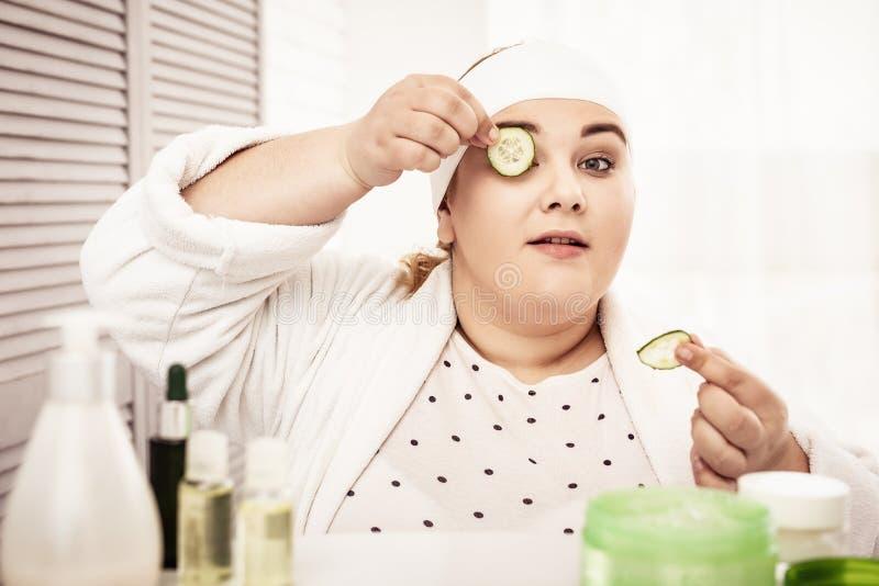 Geconcentreerde grote vrouw die komkommers op haar oogleden zetten royalty-vrije stock fotografie