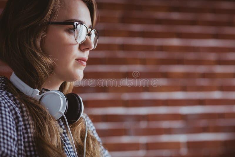 Geconcentreerde hipster onderneemster met hoofdtelefoon stock foto's