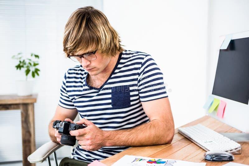 Geconcentreerde hipster zakenman die foto controleren op camera royalty-vrije stock foto's