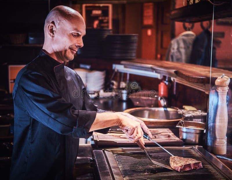 Geconcentreerde hoofdchef-kok die eenvormig kokend heerlijk rundvleeslapje vlees op een keuken in een restaurant dragen royalty-vrije stock foto
