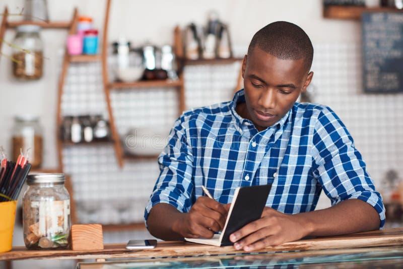 Geconcentreerde jonge Afrikaanse ondernemer die in zijn koffie werken royalty-vrije stock foto