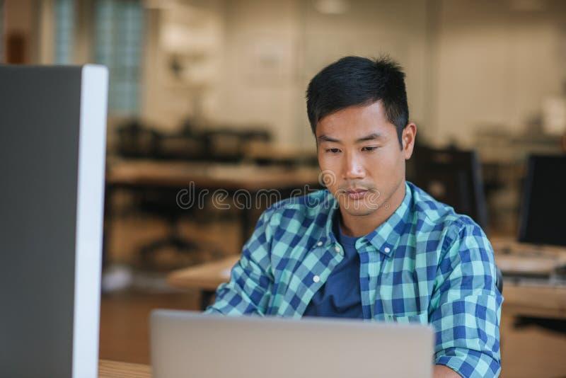 Geconcentreerde jonge Aziatische ontwerper die laptop met behulp van bij zijn bureau stock foto