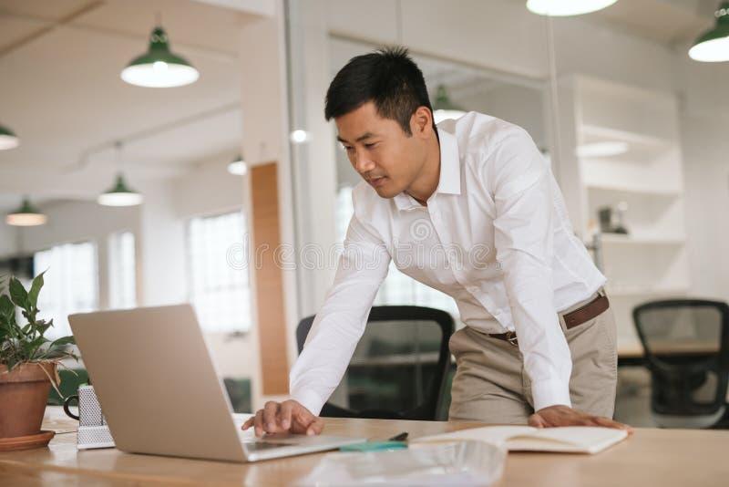 Geconcentreerde jonge Aziatische zakenman die online bij zijn bureau werken royalty-vrije stock fotografie