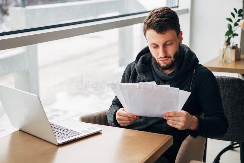 Geconcentreerde Jonge Gebaarde Werkende Laptop van Zakenmanwearing black tshirt Stedelijke Koffie royalty-vrije stock fotografie