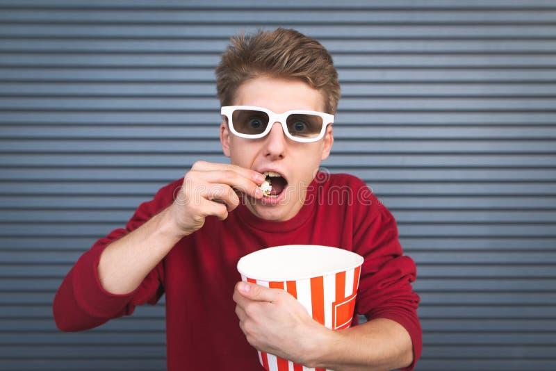 Geconcentreerde jonge mens in 3D glazen die popcorn van een kom eten en op een film op een donkere achtergrond letten stock afbeelding