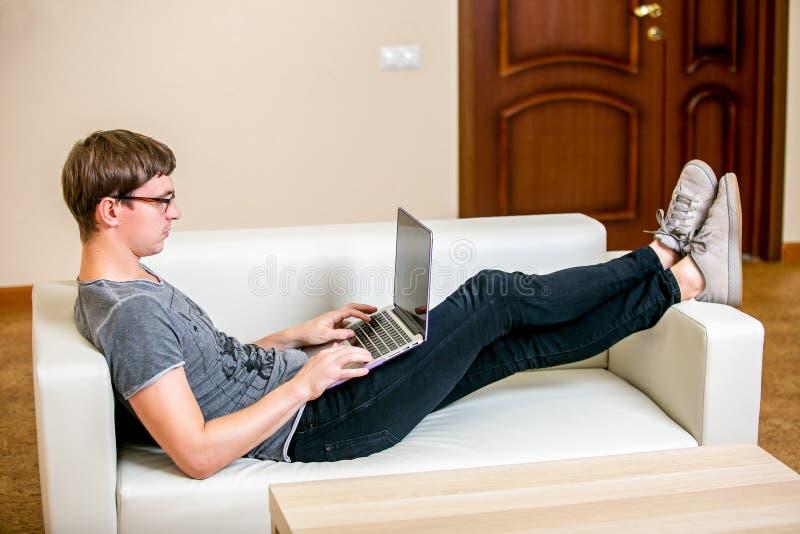 Geconcentreerde jonge mens met glazen die aan een laptop thuis bureau werken Het liggen op de laag en het typen op laptop stock foto's