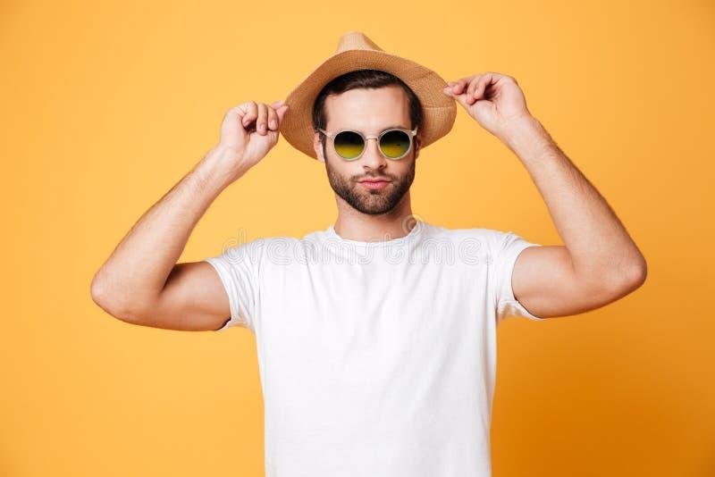 Geconcentreerde jonge mens status geïsoleerd over gele achtergrond stock afbeeldingen