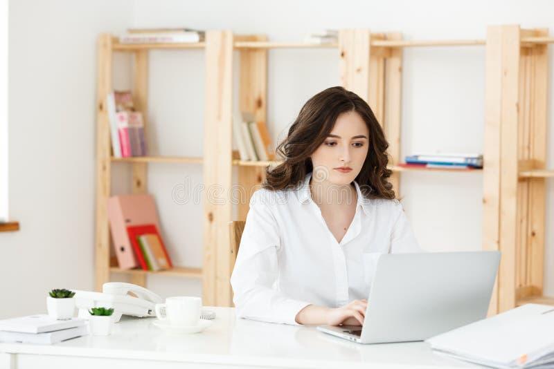 Geconcentreerde jonge mooie onderneemster die aan laptop en document in helder modern bureau werken stock foto