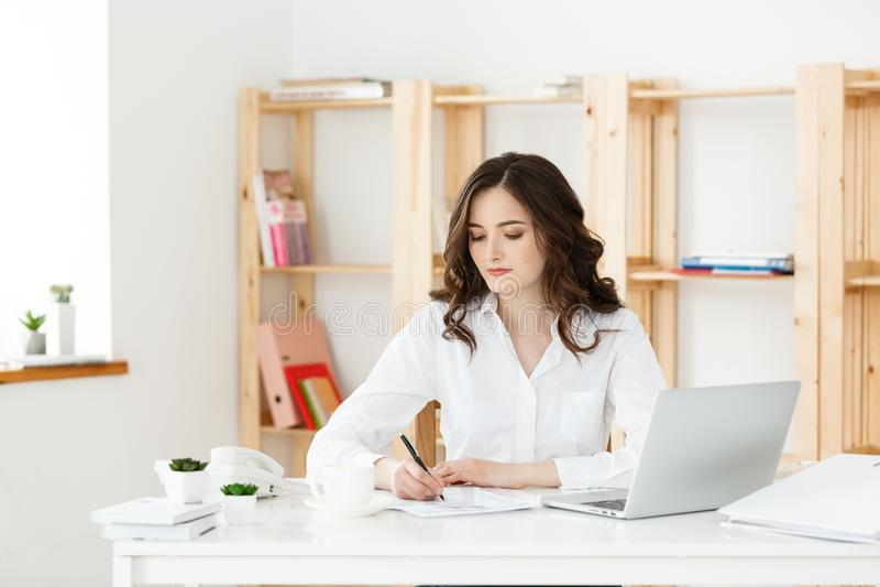Geconcentreerde jonge mooie onderneemster die aan laptop en document in helder modern bureau werken stock foto's