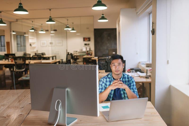 Geconcentreerde jonge ontwerperzitting bij zijn werkstation in een bureau stock foto