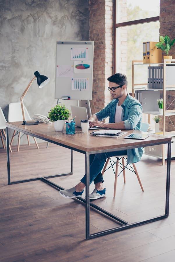 Geconcentreerde jonge slimme entrepreneuer die met computer werken en stock afbeeldingen