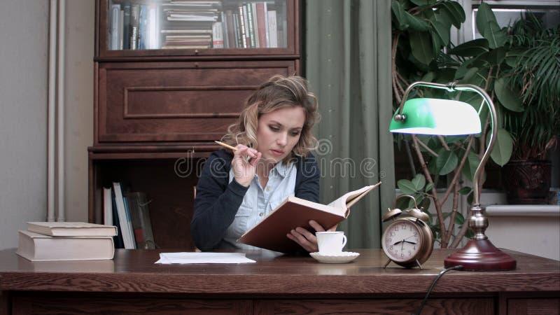Geconcentreerde jonge vrouw die een boek met een potlood in haar handen lezen, die bij een bureau zitten wanneer haar mannelijke  stock afbeelding