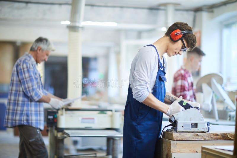 Geconcentreerde jonge werknemer die cirkelzaag strak houden terwijl cutti stock foto