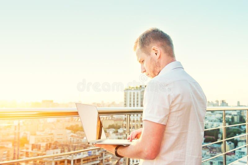 Geconcentreerde Jonge zakenman die aan laptop werken die zich op hoog stijging de bouwbalkon bevinden met zonsondergang stedelijk royalty-vrije stock fotografie