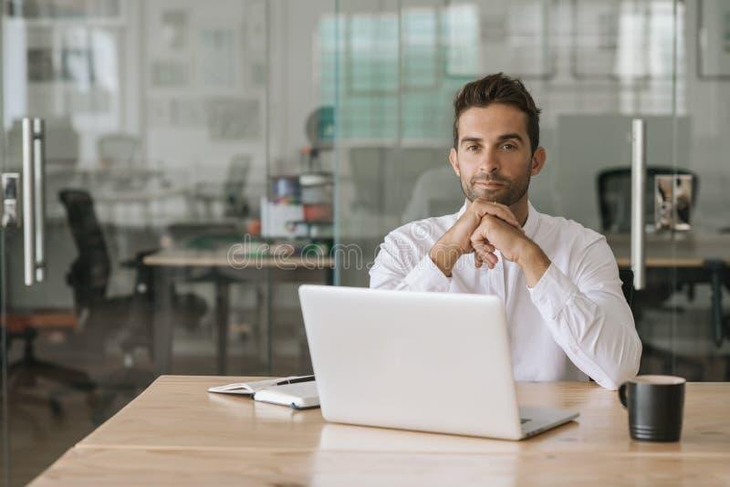 Geconcentreerde jonge zakenman die bij zijn bureau werken stock foto's